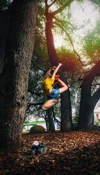 Person in Yellow Shirt and Blue Denim Shorts Doing Ballet Stance on Woods