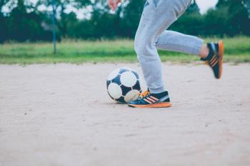 Person Kicking Soccer Ball on Gray Sand