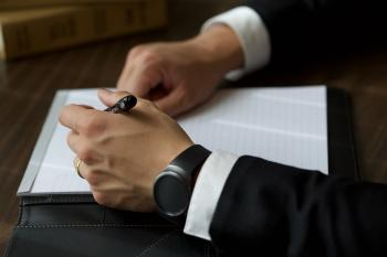 Person on Black Suit Jacket Writing on White Paper