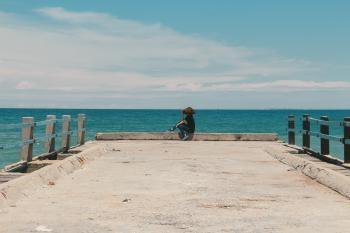 Person Sitting on the Edge of the Beach Dock