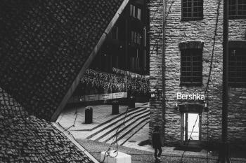 Person Standing Near Bershka Building Grayscale Photography