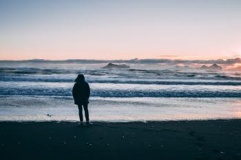 Person Standing on Beach Seashore during Sunset