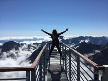 Person Standing on Hand Rails With Arms Wide Open Facing the Mountains and Clouds