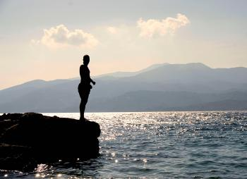 Person Standing on Rock Besides Sea Near Island during Daytime