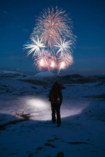 Person Stands on Snow Covered Mountain Looking at Fireworks
