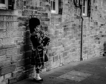 Person Using Bagpipes Near Wall in Grayscale Photography