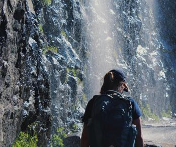 Person Walking Under Waterfalls