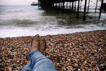 Person Wearing Blue Denim Pants and Brown Boots Sitting on Brown and Black Stone in Front of Body of Water
