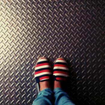 Person Wearing Red-and-multicolored Slip-on Shoes Standing on Gray Metallic Diamond Plate