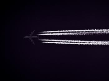 Photo of Airplane Across the Clouds during Night Time