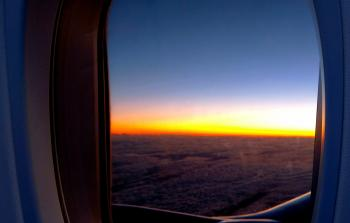 Photo of Airplane Window With View of Clouds and Golden Hour