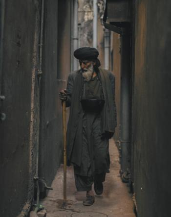 Photo of an Old Man Walking in the Alley