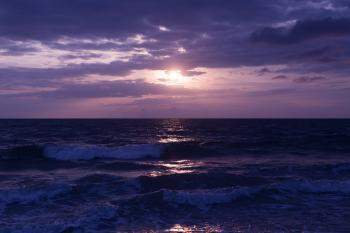 Photo of Blue Ocean and Dark Clouds during Sunset