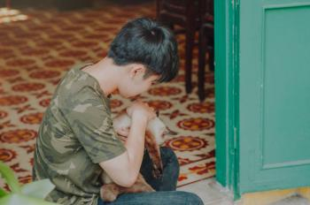 Photo of Boy Wearing Camouflage Shirt Holding a Cat