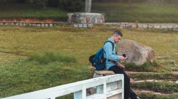 Photo of Man Sitting Near Rock