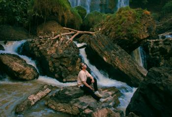 Photo of Man Sitting on Gray Rock Surrounded by Water Falls