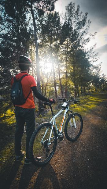 Photo of Man Wearing Red Shirt Holding White Mountain Bike