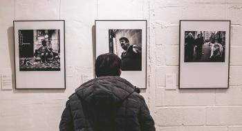 Photo of Person Standing in Front of Three Pictures