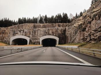 Photo of Two Highway Tunnels in Cliff Under Cloudy Sky