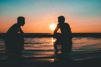 Photo of Two Men on Seashore during Sunset