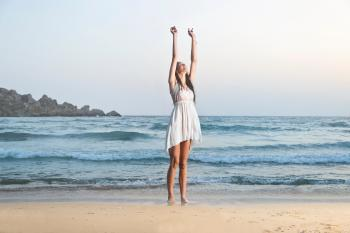 Photo of Woman in White Sleeveless Dress Raising Hands