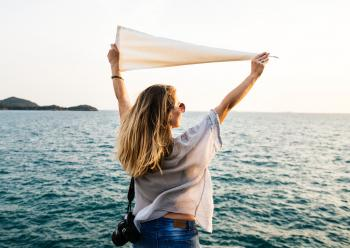 Photo of Woman Wearing White Top, Blue Bottoms and Black Dslr Camera Holding White Textile While Facing the Ocean