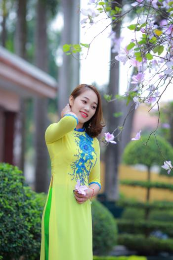 Photo of Woman Wearing Yellow and Blue Floral 3/4-sleeved Dress