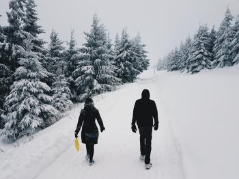 Photograph of Two Persons in the Middle of the Road on a Snowy Setting