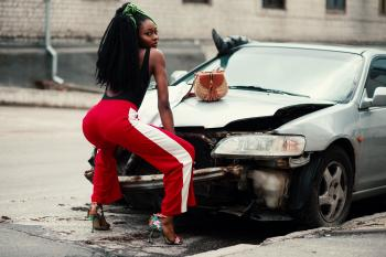 Photograph of Woman About to Twerk in Front of Vehicle