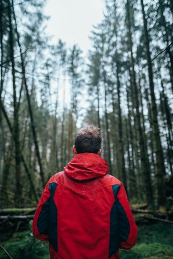 Photography of Man Wearing Black and Red Jacket Standing in Forest