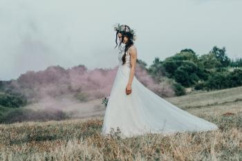 Photography Of Woman In White Wedding Dress Walking On Grass Field