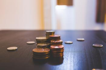 Pile of Brown Coins on Brown Wooden Table Top