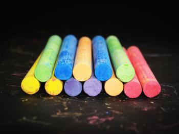 Pile of Colored Chalk on Black Wooden Tabletop