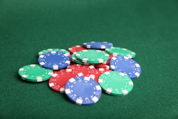 Pile of poker chips on green felt.