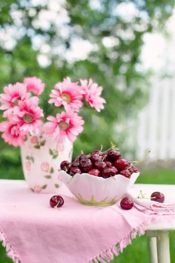 Pink Petaled Flower Beside White and Green Bowl Full of Cherry