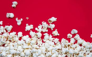 Popcorn spilled on red background