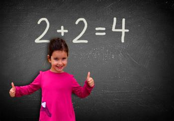 Proud assertive little girl solving a sum on blackboard