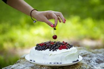 Putting cherry on the fresh berry cake