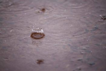 Rain drops on water puddle