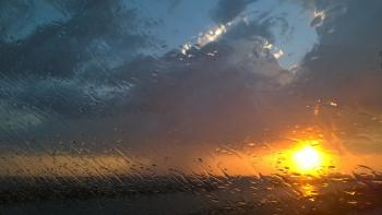 Rain on a window at sunset