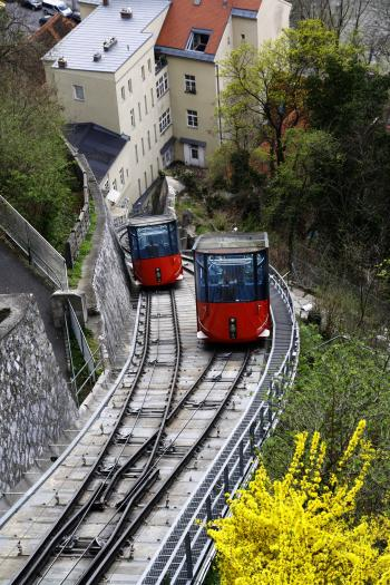 Red and Black Cable Train Uphill Near the Houses during Daytime