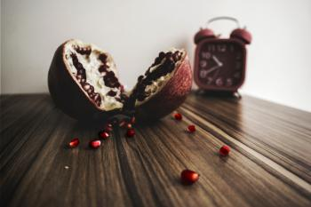 Red and White Round Fruit on Brown Wooden Table With Red Alarm Clock