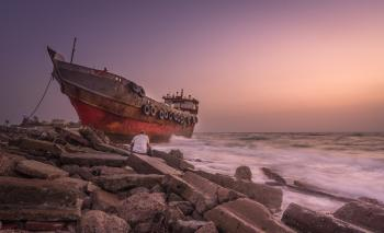 Red Blue and Black Photo of a Ship and a Man Sitting on a Stone Near Seashore