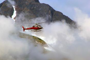 Red Helicopter on Top of Foggy Mountain