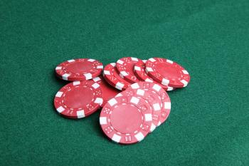 Red poker chips on green felt.