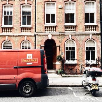 Red Royal Mail Parked Near Brown Brick Building