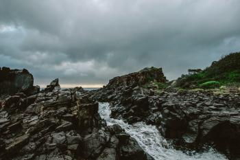Rocky River Under Cloudy Sky