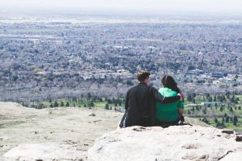 Romantic couple hugging sitting on a rock