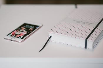 Rose Gold Iphone 6s Beside White and Black Polka Dots Book Both on Top of White Wooden Table