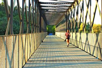 Runner crossing a metal bridge